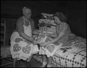 Primary view of object titled '[Aunt Nora looking at quilt patterns]'.
