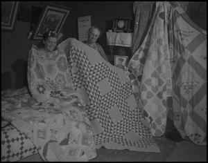 Primary view of object titled '[Aunt Nora Treece showing quilts]'.