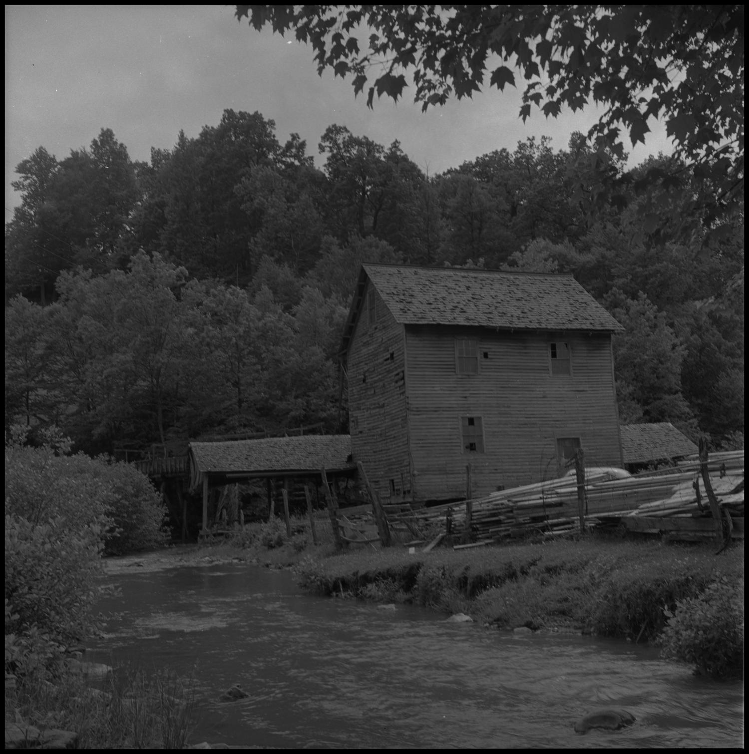 [Home by the creek], Photograph of a large two-story wooden house on the side of a creek. In the image, piles of wood boards are stacked along the fence line and large trees fill up the background.,