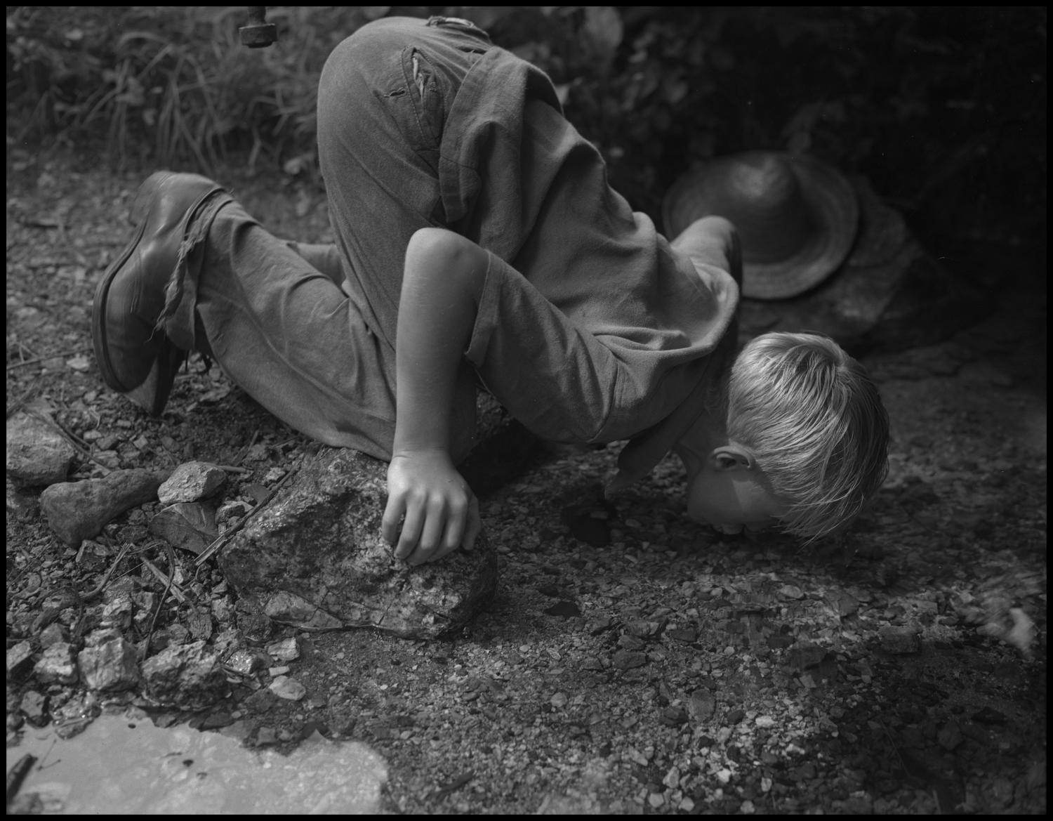 [Young boy drinking water from the creek], Photograph of an unidentified boy kneeling over to drink water from a creek. In the image, the boy is wearing a short-sleeved shirt and pants, his straw hat can be seen resting on the side of the water.,