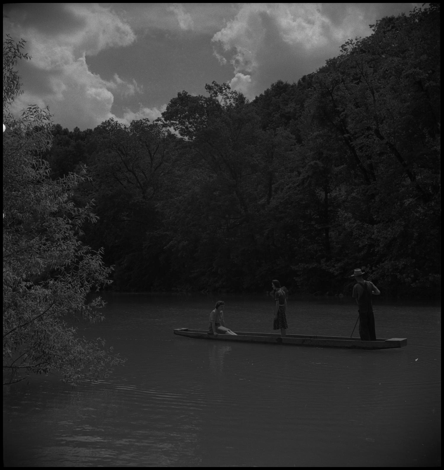 [On the canoe], Photograph of a group of three people on a canoe in the creek. In the image, the group of two girls and one boy are inside the canoe, one sitting and two standing, in the middle of a creek. Large trees go all the way to the shoreline.,