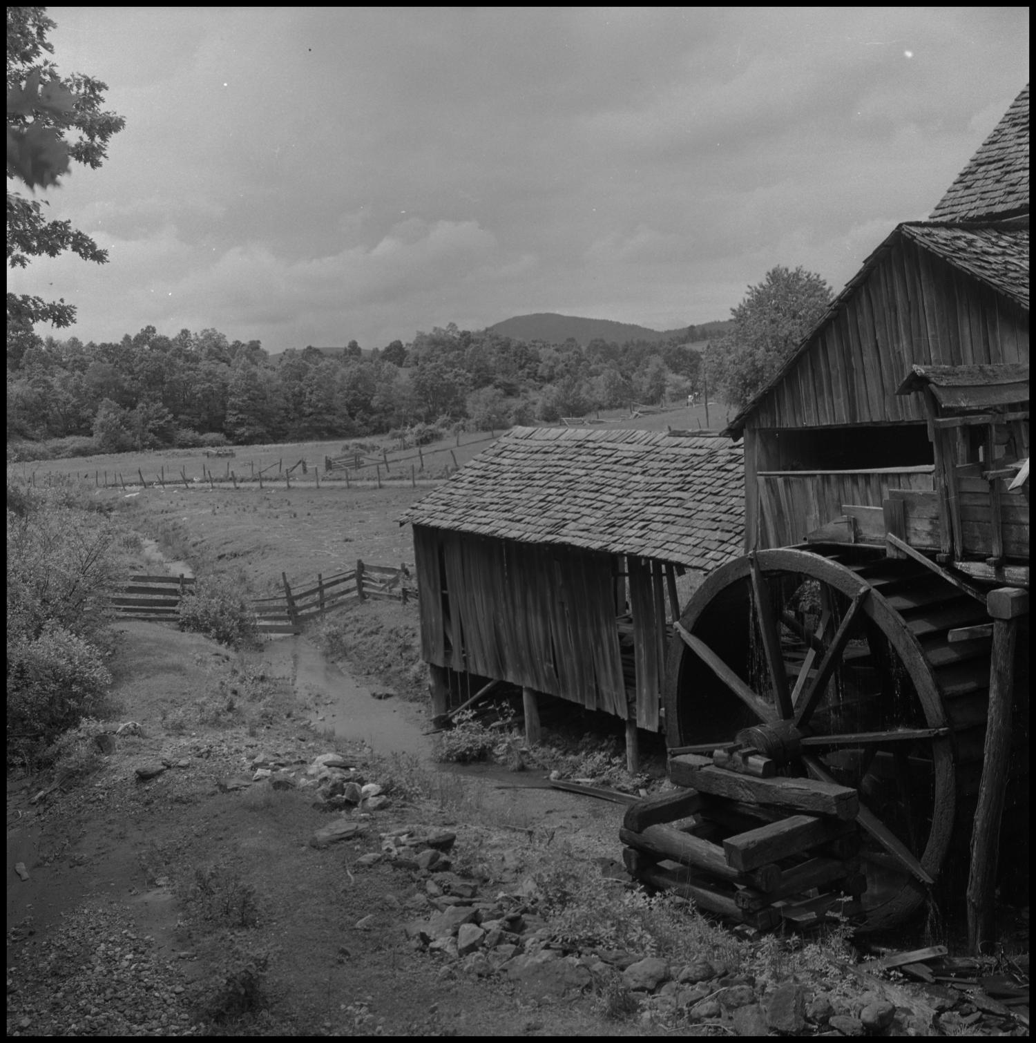[Watermill creek], Photograph of the watermill rotating into a small creek. In the image, the creek extends past the fence along a road.,