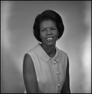 Black and white photo of a smiling African American woman, who wears a dress white tank with three white buttons on the front. She has short black hair.