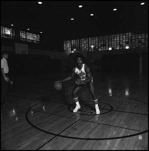 Primary view of [Unidentified basketball player dribbling ball]