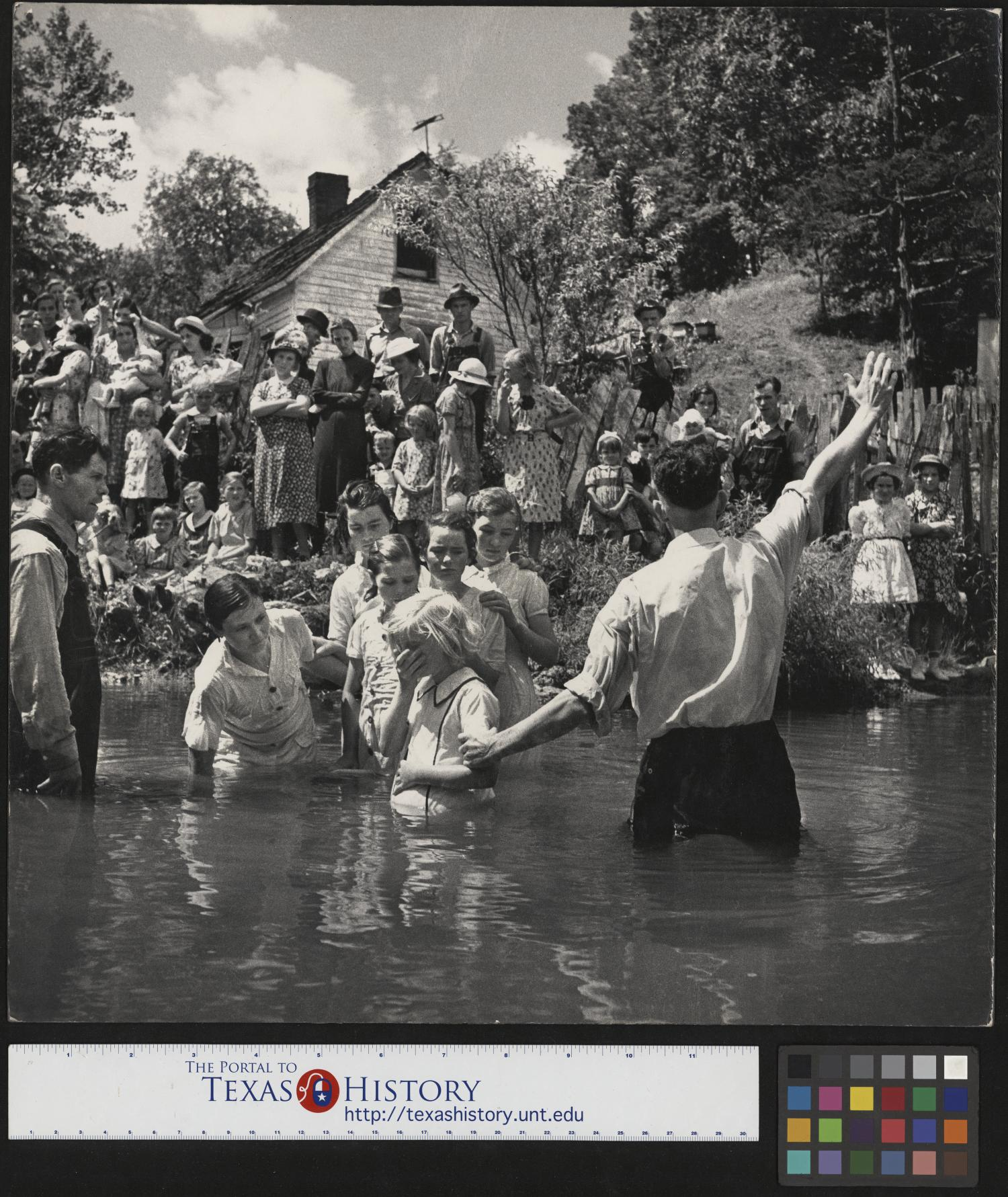 [Baptising in Olde Towne Creek], Photograph of the baptism of Ivana Wright, who is standing a creek next to Preacher Hugh Vancel; Vancel is facing the bank and raising one of his hands toward the crowd standing on the bank. Immediately behind them, Hester Welch, Minnie Hicks, Cleo McCurey, Lilian Hicks, and Lenore Treece are also in the creek, standing in line. The baptisms took place int he Olde Towne Creek outside John Owens home in Red Hill, Tennessee.,