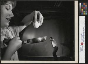 Primary view of object titled '[John Milligan prepares to scramble and egg with his Slingshot]'.