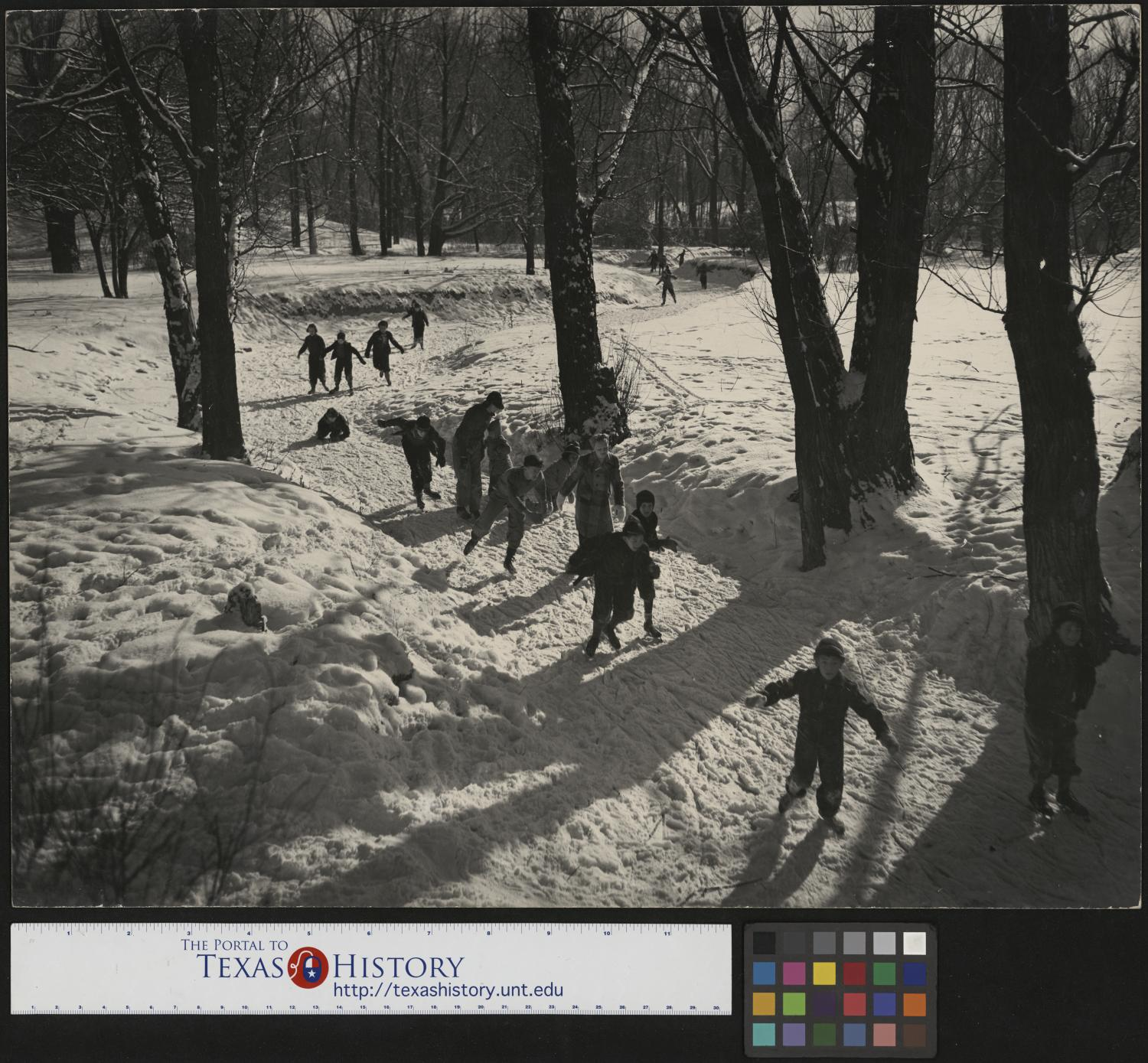 [Skating Down a Creek], Photograph of people, mostly children, ice skating down a frozen creek. In the image, the groups are trying to skate down the ice covered creek, some are falling or have fallen down.,