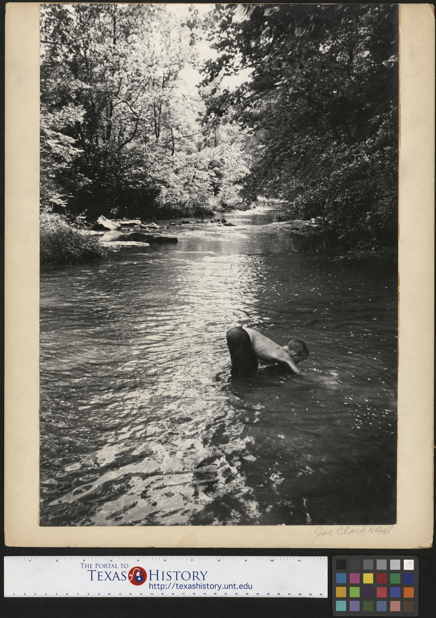 """[Mountain Boy Fishing], Photograph of Jimmy Powell, also known as """"Mountain Boy,"""" bent over in a creek in Cumberland Gap, Tennessee. In the image, Powell, shirtless, is fishing in a creek with trees lining all sides of the creek. Photographs from this series were featured in Life Magazine and titled """"Mountain Boy."""","""