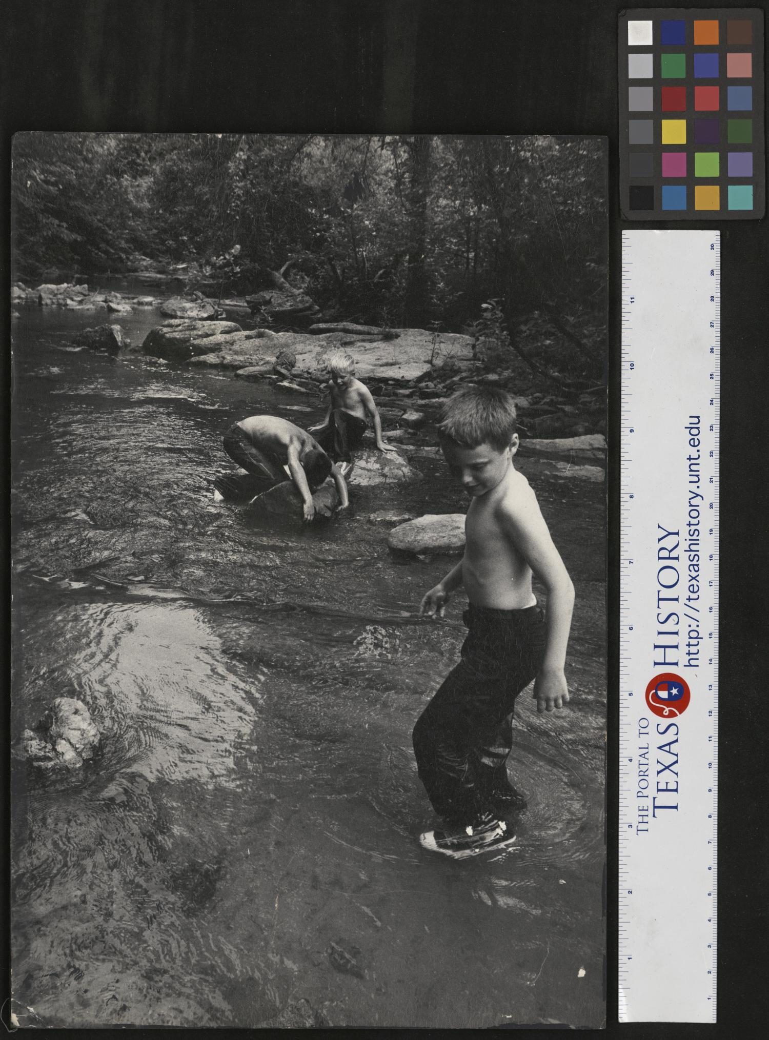 """[Boys Playing in Creek], Photograph of three boys playing in a creek, in Cumberland Gap, Tennessee. Rocks and trees line the edges of the water. Narrative by Junebug Clark: We are being taught how to catch fish with our bare hands by Jimmy Powell. In the center is my Detroit cousin Tom Krent who made trips to Tennessee with us. I, Junebug Clark am on the right. Jimmy is showing us how to feel under rocks and catch fish, or craw dads or snapping turtles. We are on my fathers farm, """"Vertical Acres"""" fishing in Keg Branch.,"""