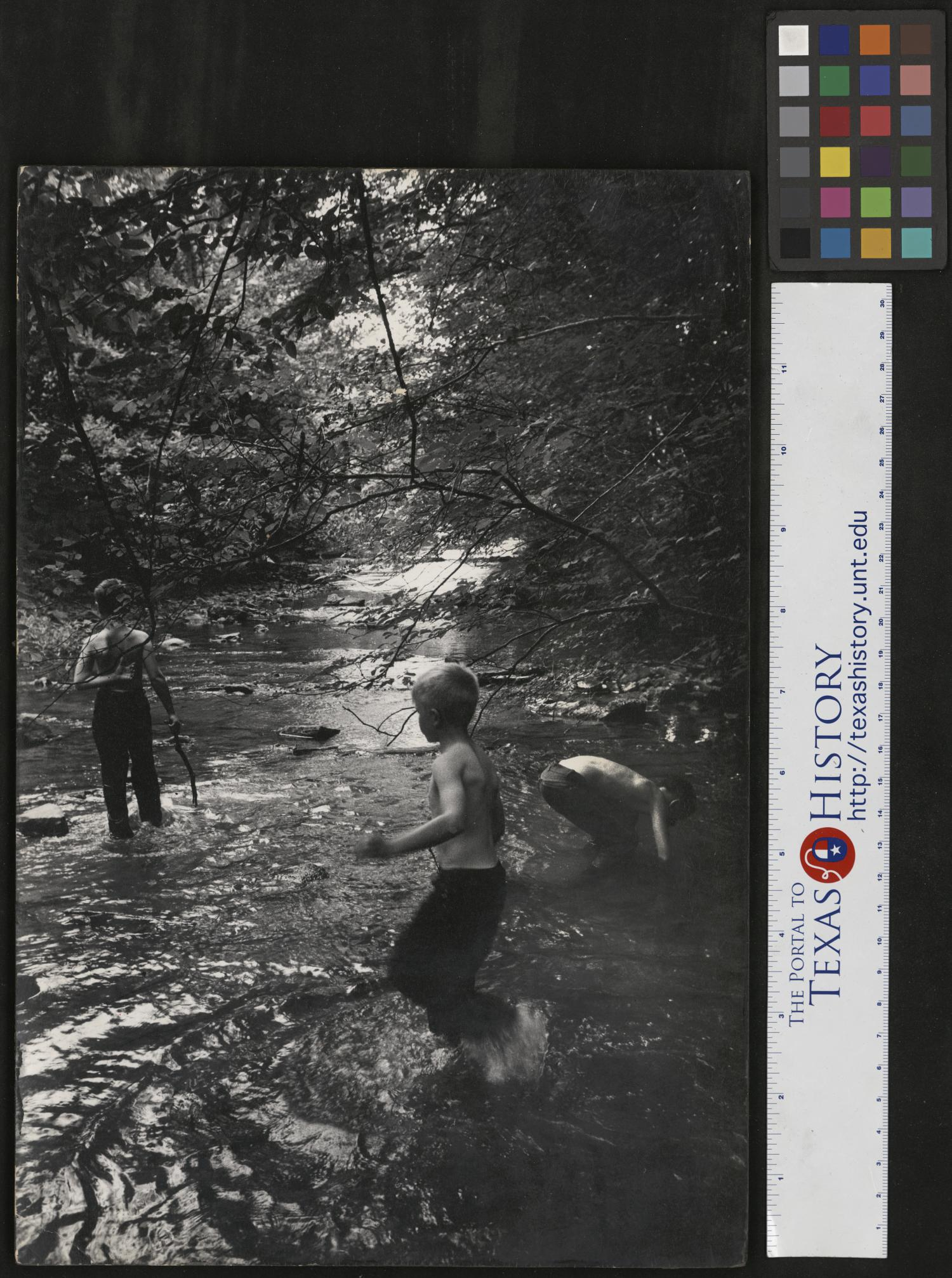 """[Boys Playing in Creek], Photograph of three boys playing in a creek, in Cumberland Gap, Tennessee. In the image, the boys are wearing pants, but no shirts in a creek lined with rocks and large trees. Narrative by Junebug Clark: We are being taught how to catch fish with our bare hands by Jimmy Powell, far right. In the center is my Detroit cousin Tom Krent who made trips to Tennessee with us. I, Junebug Clark am on the left. Jimmy is showing us how to feel under rocks and catch fish, or craw dads and snapping turtles. We are on my fathers farm, """"Vertical Acres"""" fishing in Keg Branch. Photo by: Joe Clark, HBSS. Clark PhotoFile: 0000-0015-32 mounted on wood,"""