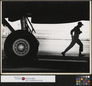 Primary view of object titled '[Aircraft worker hurries away from the plane]'.