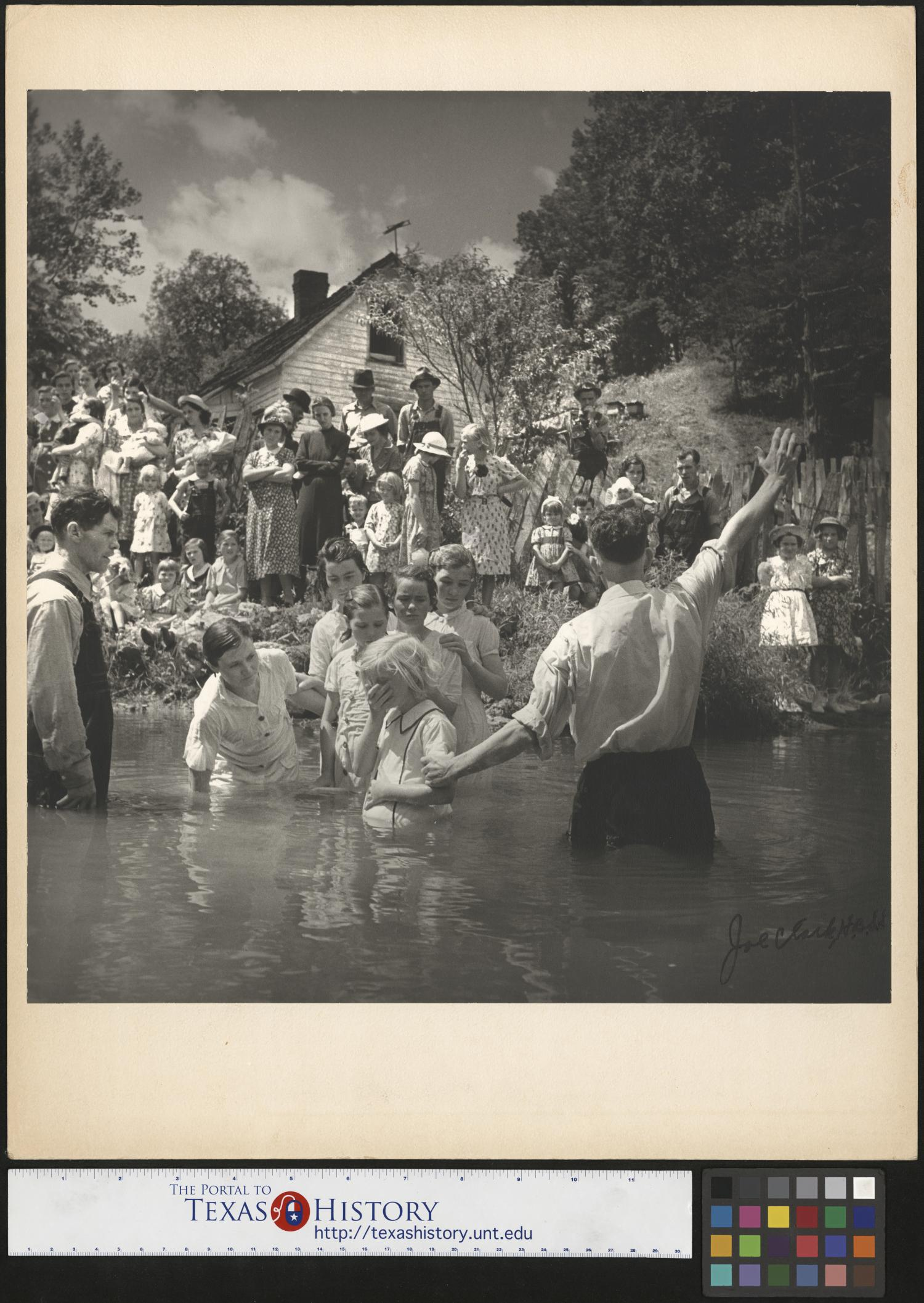 [Baptism in Olde Towne Creek], Photograph of the baptism of Ivana Wright, who is standing a creek next to Preacher Hugh Vancel; Vancel is facing the bank and raising one of his hands toward the crowd standing on the bank. Immediately behind them, Hester Welch, Minnie Hicks, Cleo McCurey, Lilian Hicks, and Lenore Treece are also in the creek, standing in line. The baptisms took place int he Olde Towne Creek outside John Owens home in Red Hill, Tennessee.,