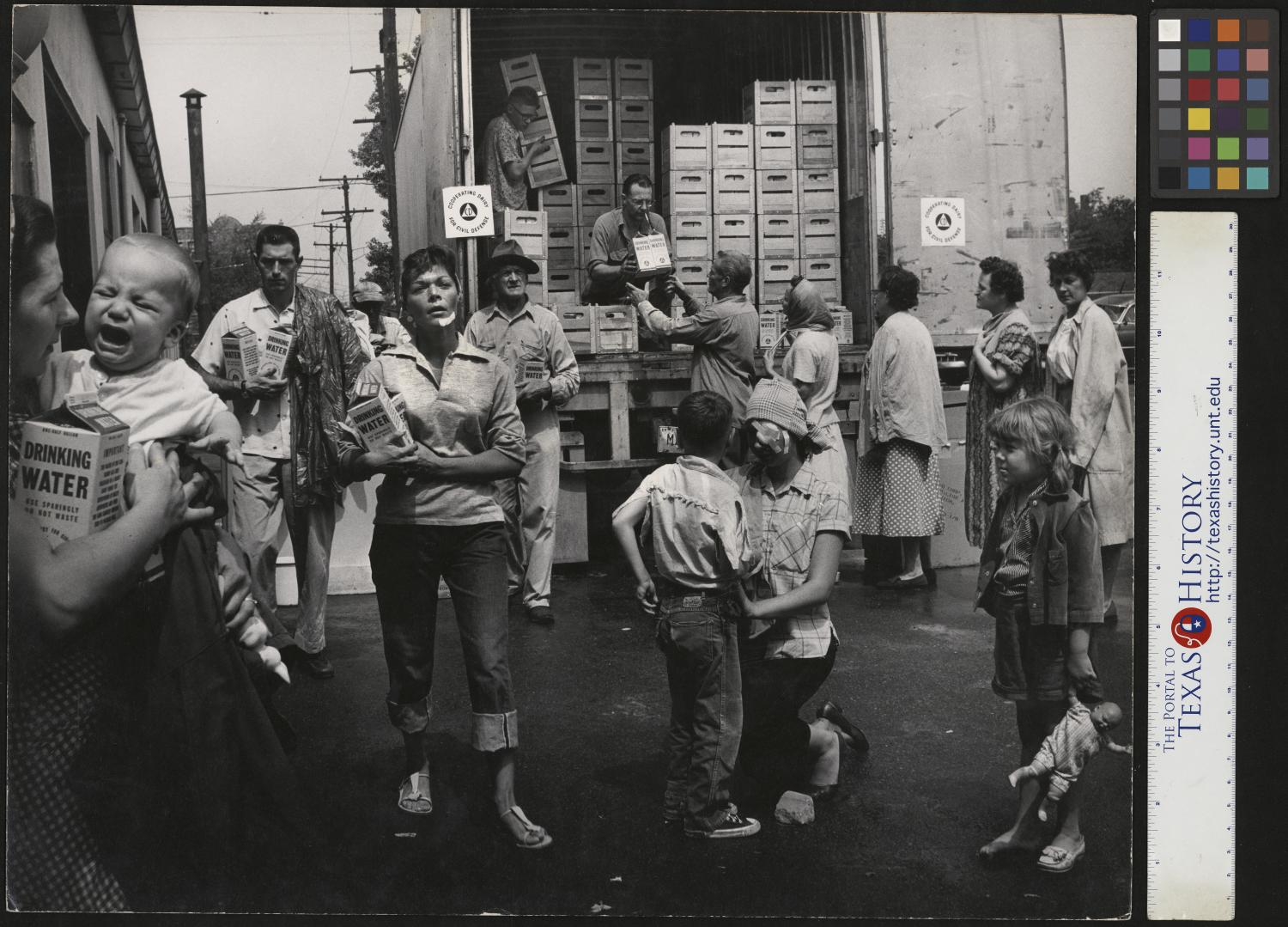 "[Receiving Water Rations], Photograph of men, woman, and children receiving two cartons of Drinking Water from the back of a truck. In the image, a line has formed for the cartons where two men inside the truck are handling the crates, a mother is consoling a crying baby in her arms, another mother, wearing bandages on her face, is fixing her sons pants. Two men and an injured woman are walking with their rations towards the camera. Narrative by Junebug Clark: Water Delivery to Florida Hurricane Disaster Victims (Re-creation) Highland Park, Michigan Photo: Joe Clark HBSS 1955 This photo is significant because in the early 50s milk was only being distributed in glass bottles. Pure-Pak was manufacturing ""New"" paper carton containers, but people were reluctant to buy milk in anything but a glass bottle. There are a series of photos in the Clark Family Photography Collection used in ads to promote the benefits of the paper carton over the glass bottle, but nothing really changed the peoples opinion until… …a hurricane hit Florida and Excello, the parent company of Pure-Pak, sent truck loads of emergency drinking water in Pure-Pak paper cartons and people finally got it. Why send glass bottles to an area already covered in broken glass? These darn things work. Since there were no photos of the unanticipated and successful distribution of paper cartons of Drinking Water, this photo is a recreation of the event. My mother, Bernice (back row second from right) was tasked early one morning, to call neighbors and friends to come to the parking of our studio, ""Immediately, dressed just as you are to our studio parking lot) Soon afterwards, the cardboard ""Milk Carton"" as opposed to the glass ""Milk Bottle"", made it into everyday life and into your refrigerator today. Photo by: Joe Clark, HBSS. https://digital.library.unt.edu/ar…/67531/metadc499295/…/1/… ...,"