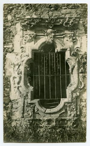 Photo of a window with silver bars. On the outside of the window is a stone wall.