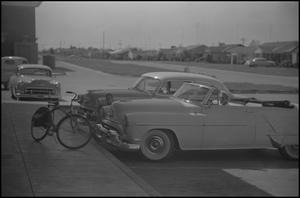 Primary view of object titled '[Cars, bicycle, and child]'.