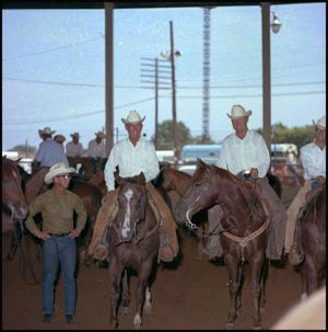 Primary view of object titled '[Standing next to men on horses]'.
