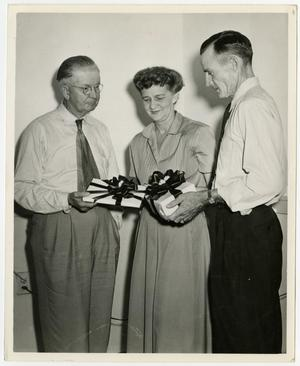 Primary view of object titled '[Fowler, Babb, and Hannah stand with gifts]'.