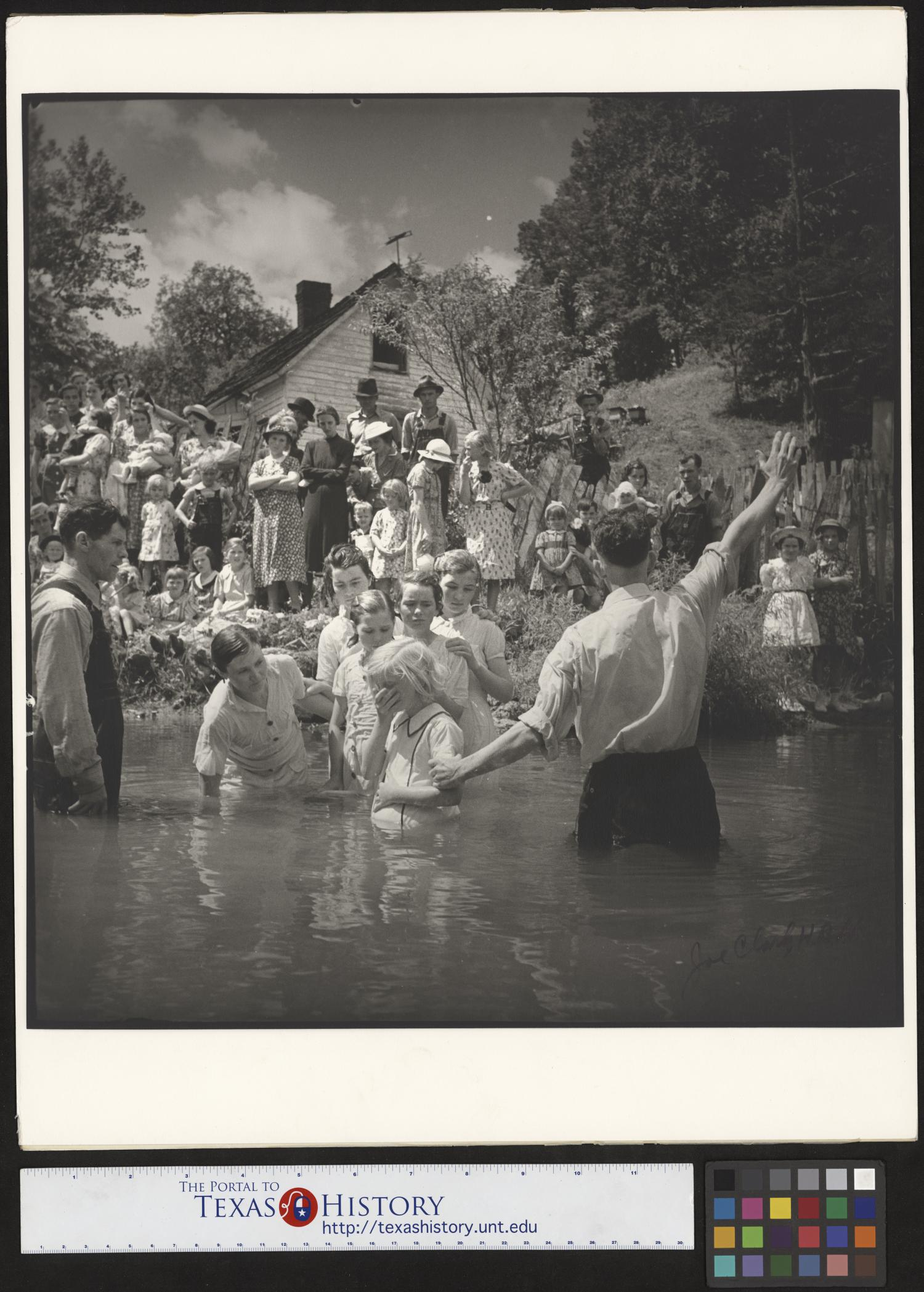 [Baptising in Olde Towne Creek (1)], Photograph of Reverend Hugh Vancel performing a baptism in Olde Town Creek near Red Hill, Tennessee. The reverend is standing in the creek and facing a large crowd of people on the bank, and holding the arm of a young girl standing next to him; several other girls, a woman and a man are also standing in the creek, on the left. A building with wood siding is visible in the background.,