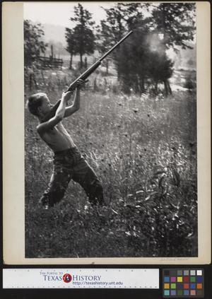 Primary view of object titled '[Jimmy Powell Firing His Rifle]'.
