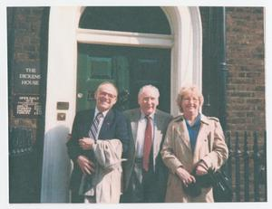 3 people, two men and one woman on the right stand side by side each other. They are in front of a green door. To the left of the door is a sign that says The Dickens House.