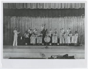Black and white photo of a band on a stage/ They are all wearing a white uniform.