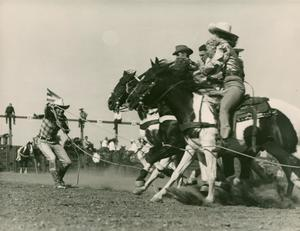 Four people on black horses are on the right of the photo. On the left of the photo, a woman pulls a rope. The rope is around the group of people on horses.