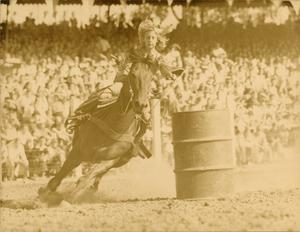 A blonde woman rides a horse around a barrel on the right side of the photo. Behind them are stands full of people.