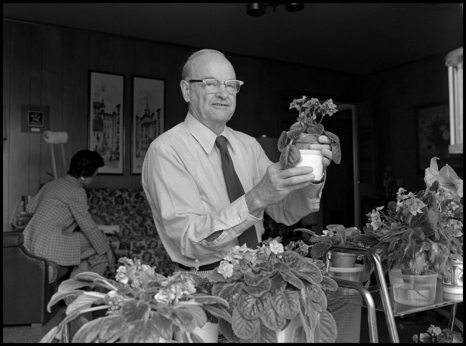 [Garland Brookshear placing pansies in new pot], Photograph of Garland Brookshear, a member of the Management faculty at NTSU, placing a potted plant, that appears to be pansies, into a larger pot. He is being photographed for his retirement.,