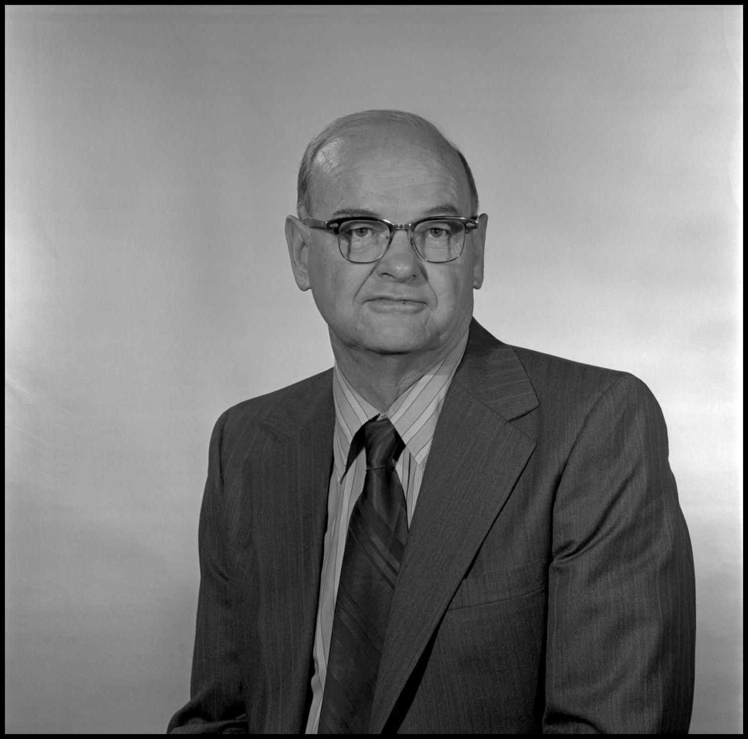 [Garland Brookshear portrait photo], Photograph of Garland Brookshear, a member of the Management faculty at NTSU, sitting for a portrait photo. He is wearing a suit with a striped shirt and tie, as well as a pair of glasses.,