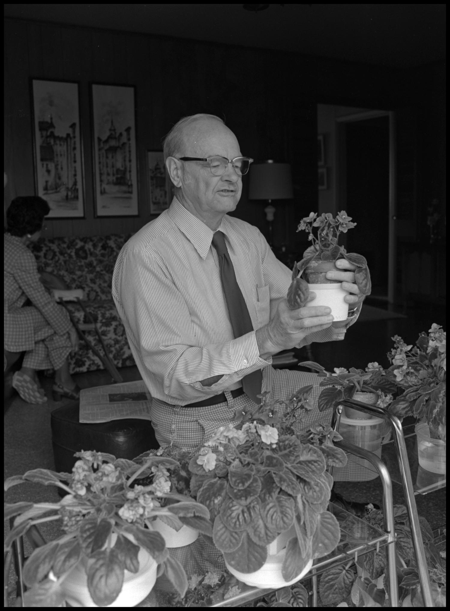 [Garland Brookshear placing a plant into a pot], Photograph of Garland Brookshear, a member of the Management faculty at NTSU, placing a pansy into a larger pot. Behind him a woman sitting on a couch is visible. Brookshear is being photographed for his retirement.,