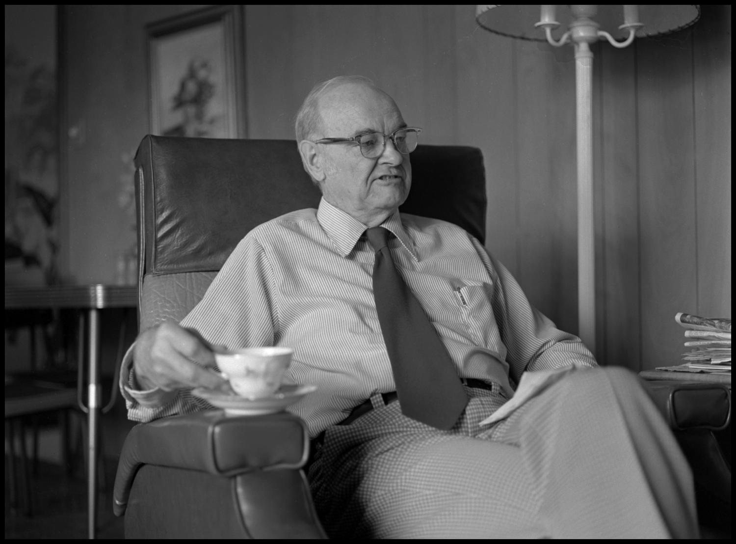 [Garland Brookshear sitting in chair with teacup], Photograph of Garland Brookshear, a member of the Management faculty at NTSU, sitting in an easy-chair with his teacup placed on the armrest. He is lifting it off of the saucer and appears to be saying something. Brookshear is being photographed for his retirement.,