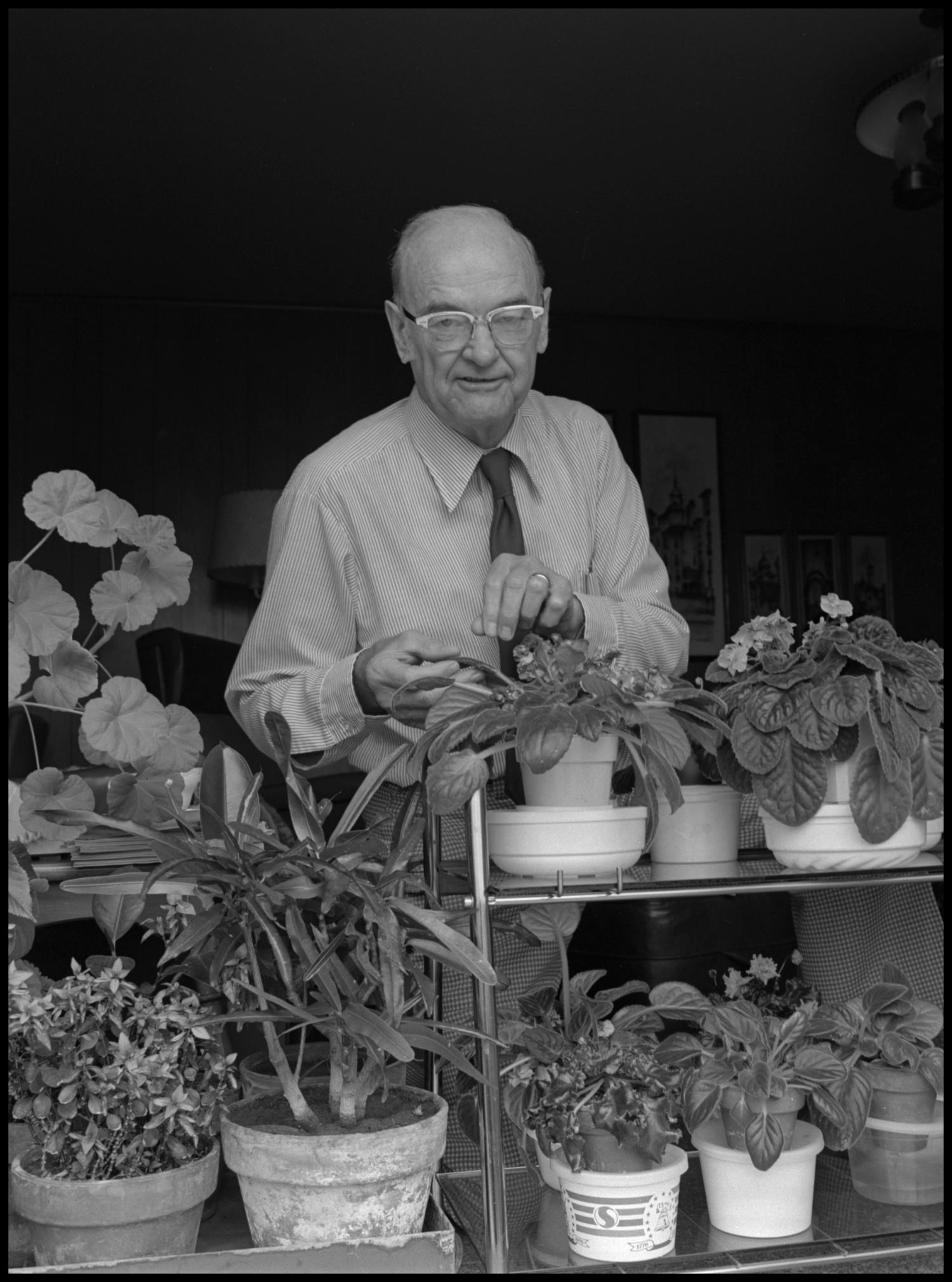 [Garland Brookshear standing with plants], Photograph of Garland Brookshear, a member of the Management faculty at NTSU, standing with his potted plants. There are small flowers as well as larger greenery. Brookshear is being photographed for his retirement.,