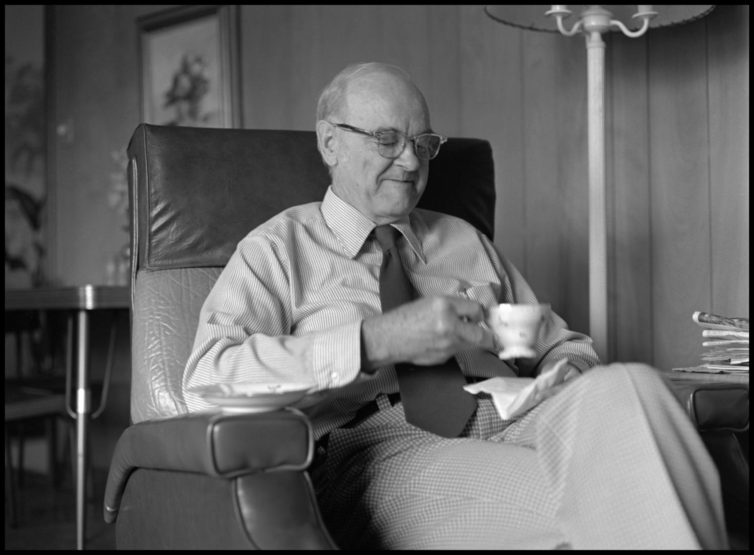 [Garland Brookshear looking at his teacup], Photograph of Garland Brookshear, a member of the Management faculty at NTSU, sitting in an easy-chair and holding his teacup. The saucer is still on the armrest. Brookshear was being photographed for his retirement.,