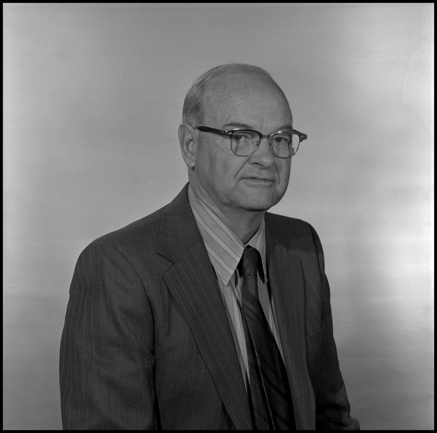 [Portrait photo of Garland Brookshear], Photograph of Garland Brookshear, a member of the Management faculty at NTSU, sitting for a portrait photo. He is wearing a suit with a striped shirt and tie, as well as a pair of glasses.,