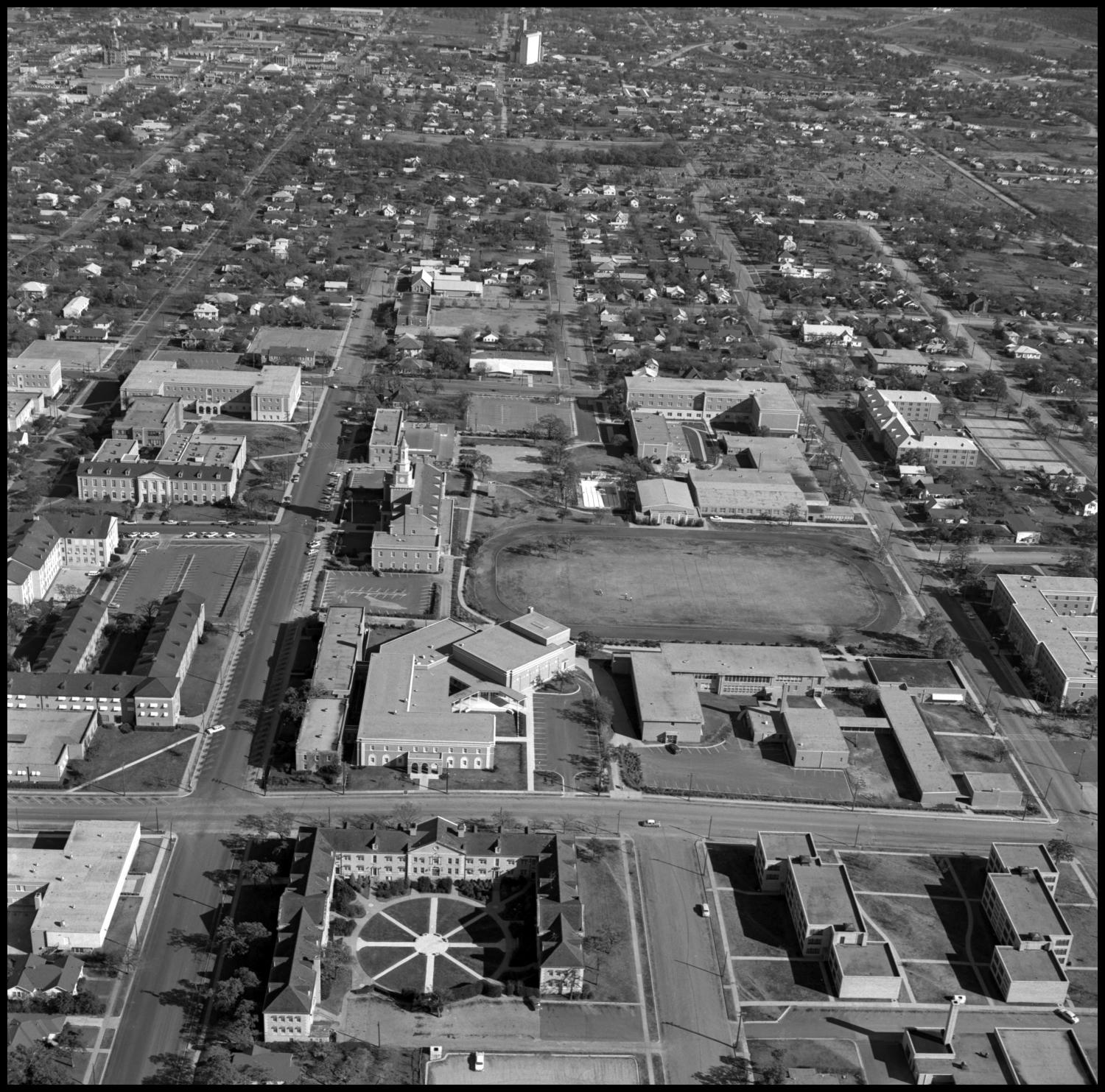 [Aerial of NTSU from the West], Aerial photograph of the NTSU campus from the west. The buildings visible in the photo are the Quadrangle Dormitories, Chilton Hall, the University Hospital, Bruce Hall, the Music Hall/Orchestra Hall, the Music Building, the Mens Building, the Laboratory School, Crumley Hall, Eagle Park, Kendall Hall, the Education-Home Economics Building, the Womens Gymnasium, the Journalism Building, the Laboratory School Gymnasium, the Memorial Union, the Administration Building, the Library Building, the Language-Government Building, and the Business Administration Building. Avenue C runs across the image left to right and intersects with Chestnut and Highland Streets.,