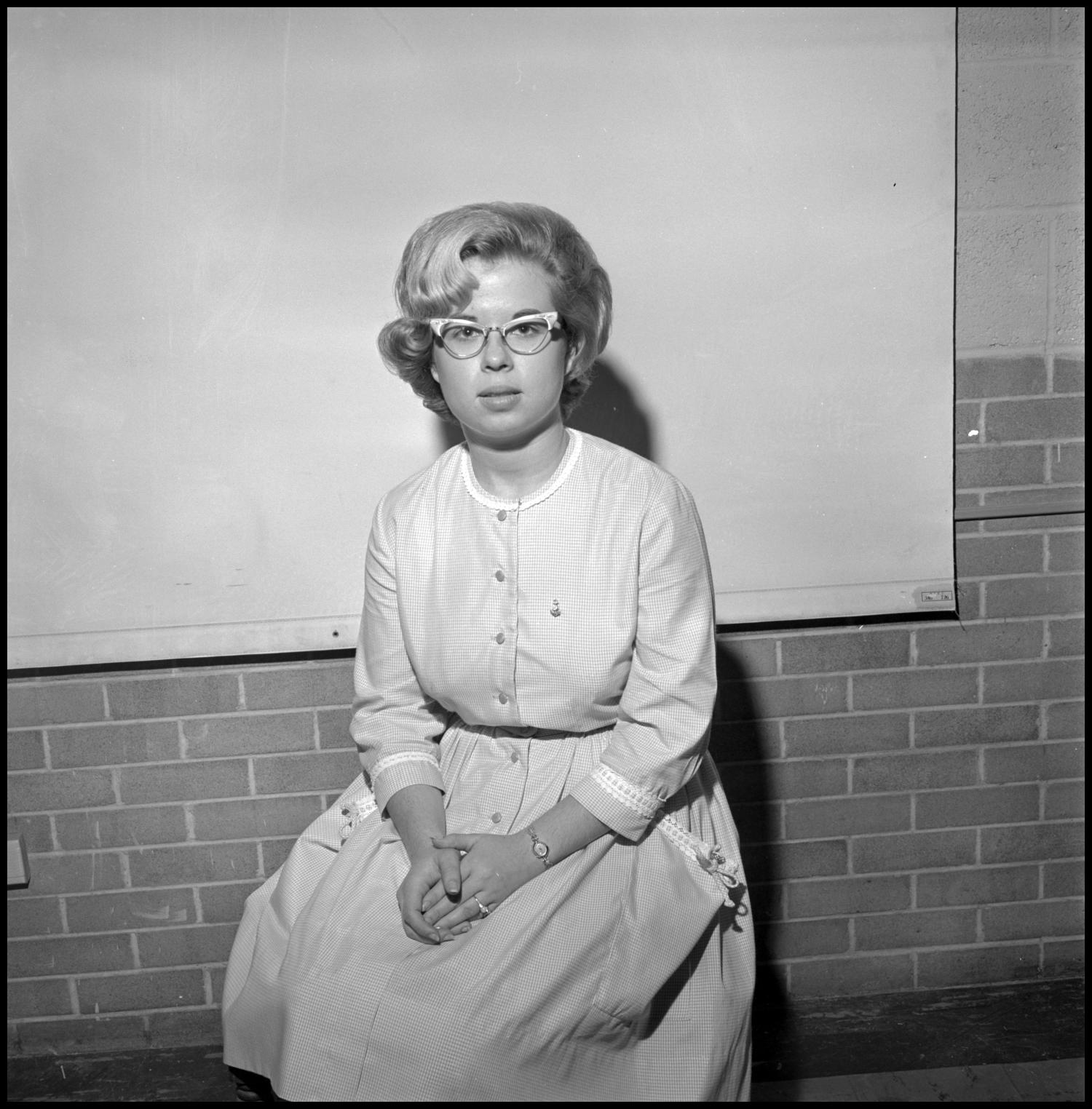 [Donna Butts portrait], Photograph of Donna Butts, a Speech and Drama major at NTSU, sitting for a portrait photo. She is wearing a dress with large pockets, trim around the collar, sleeves, and pocket tops, and buttons down the front. Her glasses are cat-eye style and she has a ring on her finger.,