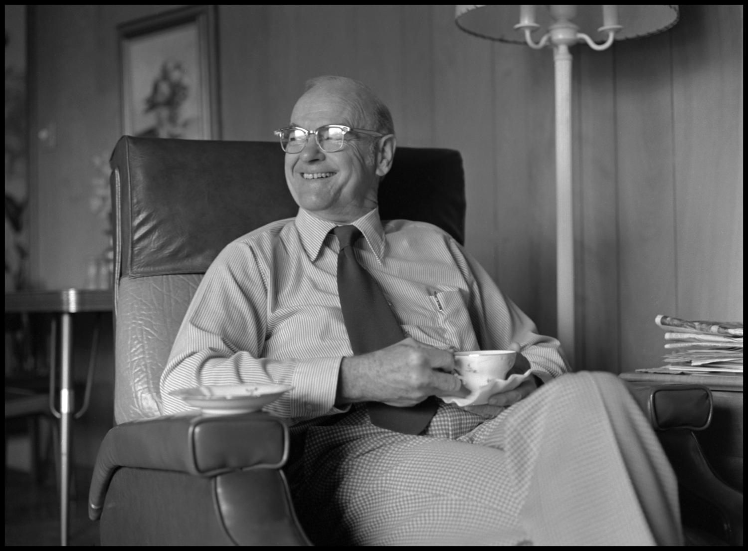 [Garland Brookshear holding his teacup], Photograph of Garland Brookshear, a member of the Management faculty at NTSU, sitting in an easy-chair and holding his teacup. The saucer is still on the armrest and he is looking to the side and laughing. Brookshear was being photographed for his retirement.,