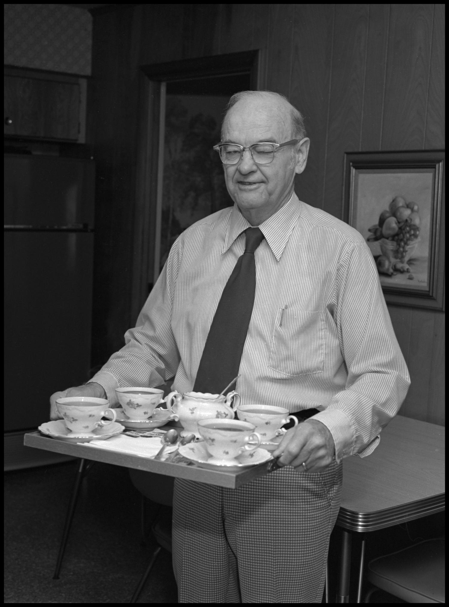 [Garland Brookshear carrying a tea tray], Photograph of Garland Brookshear, a member of the Management faculty at NTSU, carrying a tea tray for guests. Behind him is a table and a fridge. Brookshear is being photographed for his retirement.,
