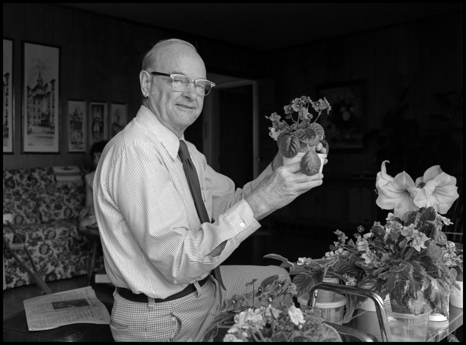 [Garland Brookshear holding up pansies], Photograph of Garland Brookshear, a member of the Management faculty at NTSU, holding a potted plant that appears to be pansies. He is being photographed for his retirement.,