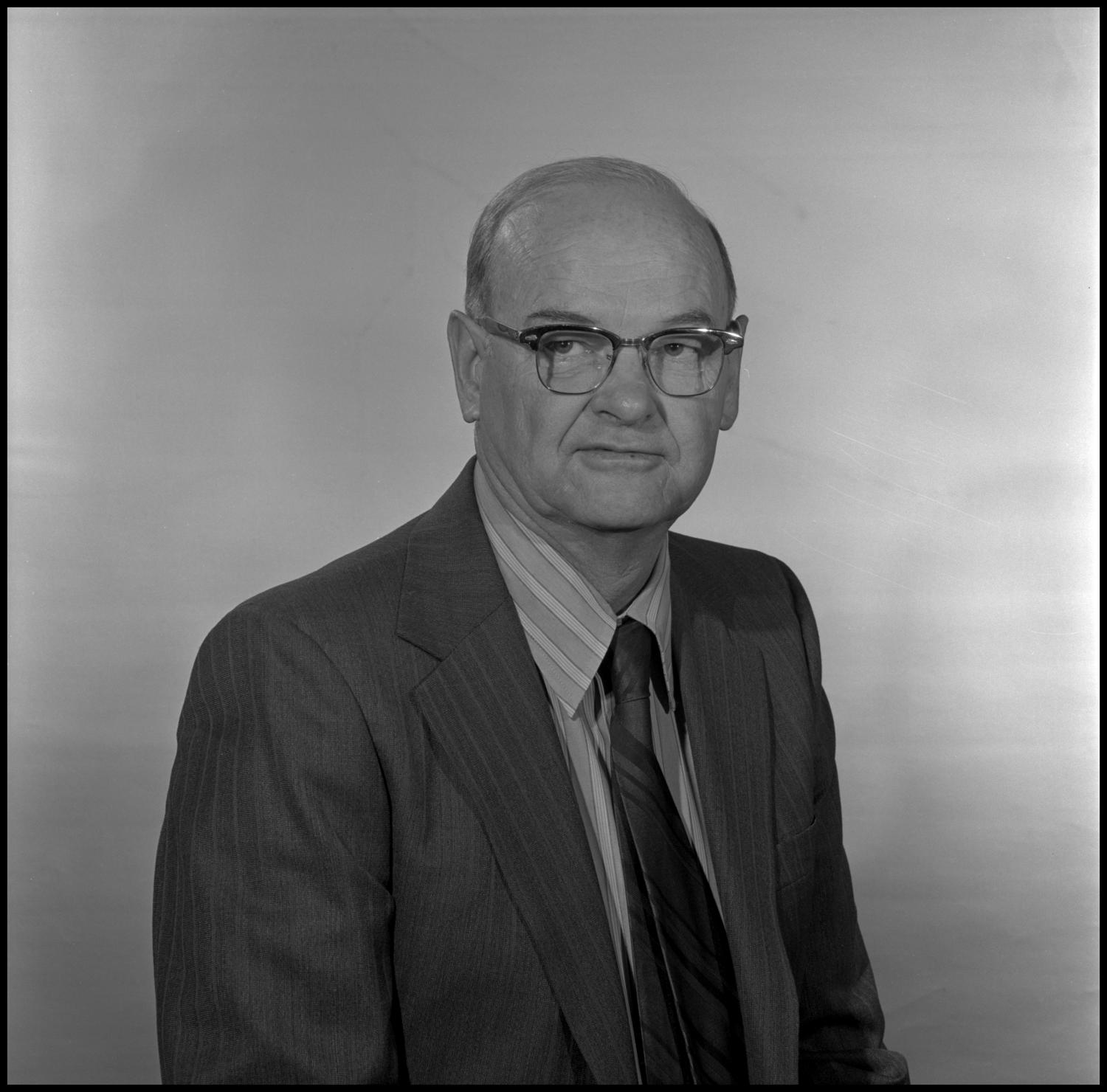 [Garland Brookshear sitting for portrait], Photograph of Garland Brookshear, a member of the Management faculty at NTSU, sitting for a portrait photo. He is wearing a suit with a striped shirt and tie, as well as a pair of glasses.,