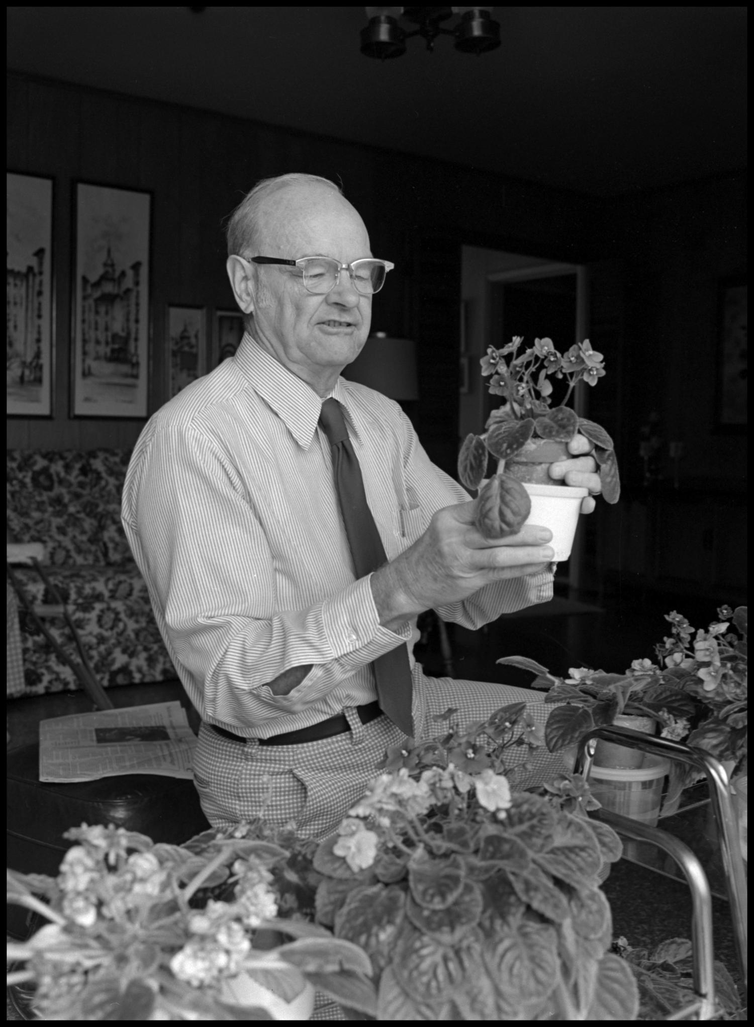 [Garland Brookshear holding pansies and new pot], Photograph of Garland Brookshear, a member of the Management faculty at NTSU, holding a potted plant, that appears to be pansies, next to a larger pot. He is being photographed for his retirement.,