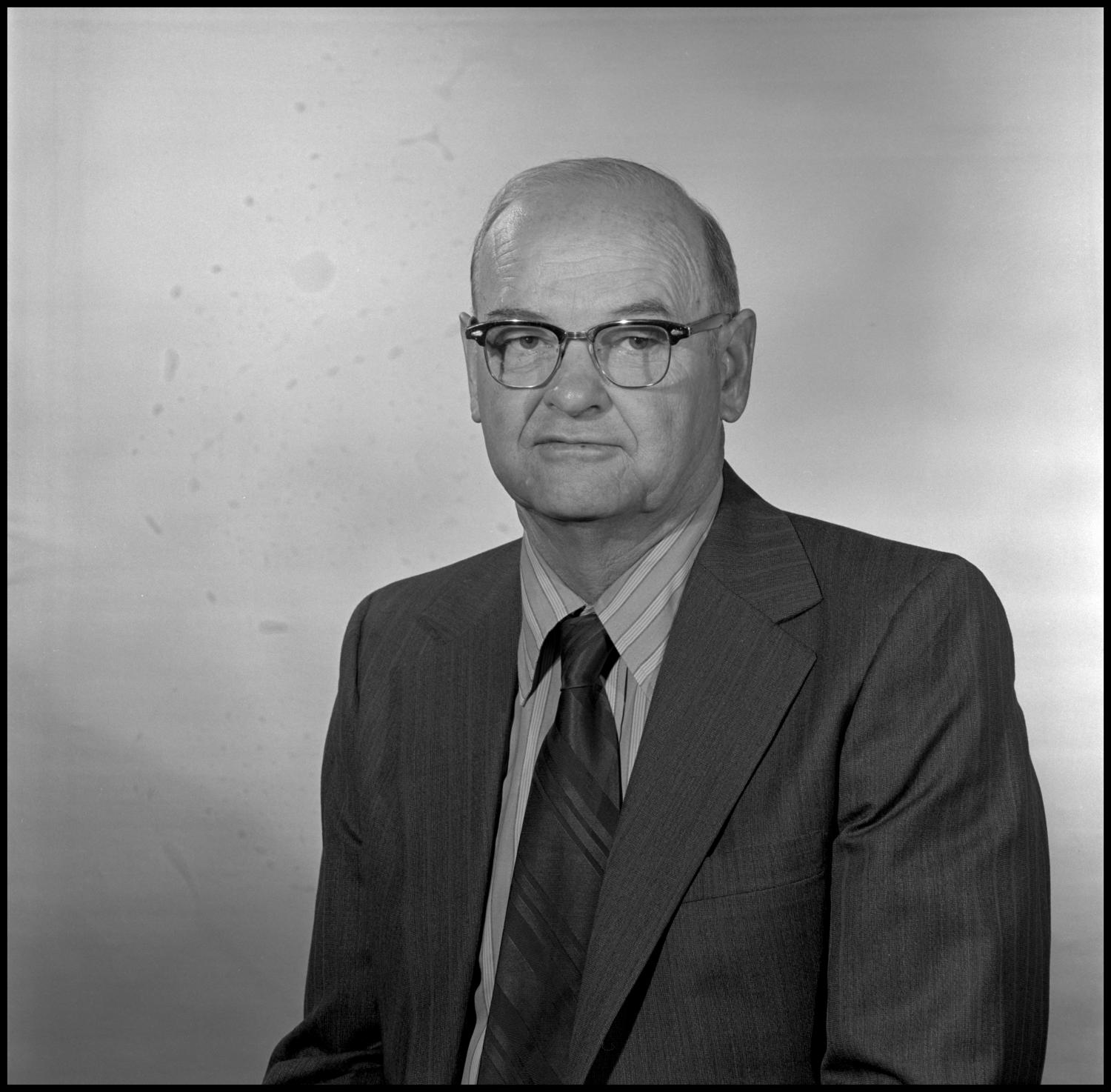 [Portrait of Garland Brookshear], Photograph of Garland Brookshear, a member of the Management faculty at NTSU, sitting for a portrait photo. He is wearing a suit with a striped shirt and tie, as well as a pair of glasses.,