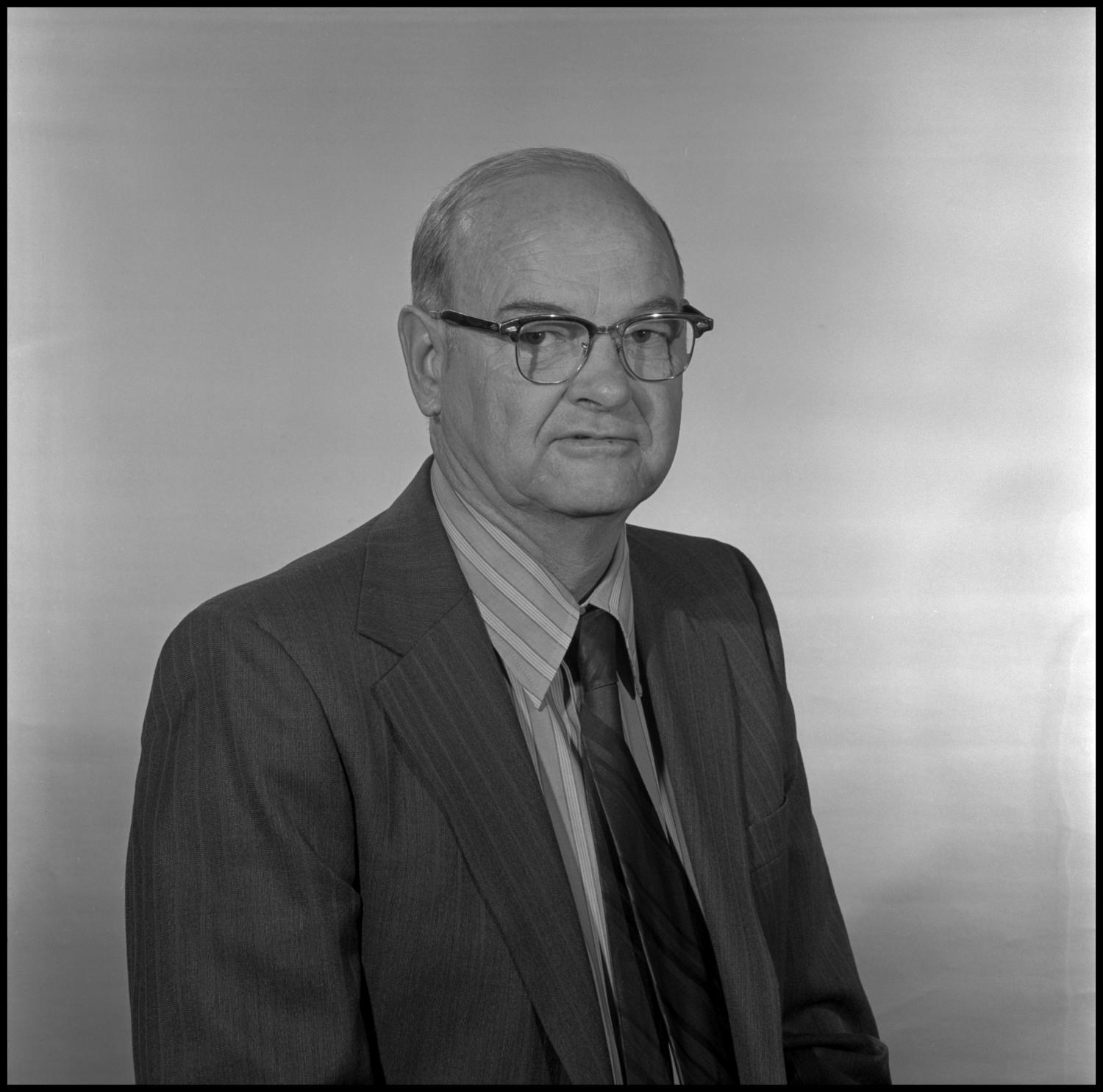 [Garland Brookshear portrait], Photograph of Garland Brookshear, a member of the Management faculty at NTSU, sitting for a portrait photo. He is wearing a suit with a striped shirt and tie, as well as a pair of glasses.,