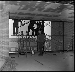 Black and white photograph inside of a building, looking at workers standing on scaffolding outside of an opening in the wall. One man stands inside wearing a hardhat, with ladders nearby.