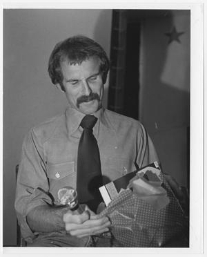 Primary view of object titled '[Bill Nelson opening a gift]'.