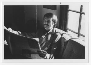 Primary view of object titled '[Bill Nelson smiling over a paper]'.