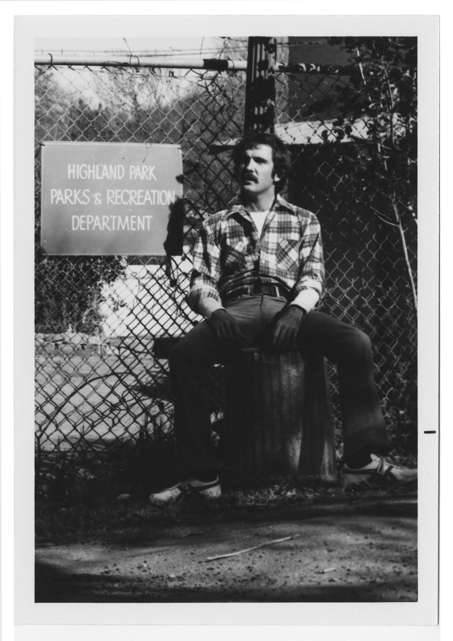 [Bill Nelson sitting by sign], Photograph of Bill Nelson sitting next to a Highland Park, Parks and Recreation Department sign.,
