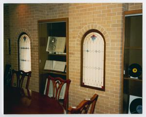 Color photograph of two display cases between two stained glass windows. In the foreground is a wood table and chairs.