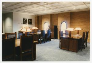 Color photograph a room with three large wood table and chairs. Each table has a lamp at either end.