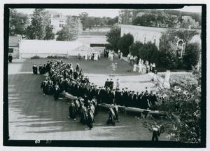 Una fotografía en blanco y negro de estudiantes con uniforme de graduación marchando por un patio.